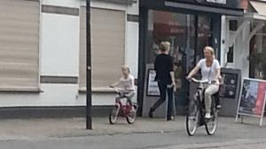 Dutch village scene with adult on cycle lane and child on pavement